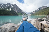 Personal perspective view of a young woman relaxing by the lakeshore at Lake Louise in Banff national park, Canada