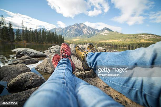 Personal perspective of two people relaxing by the lake