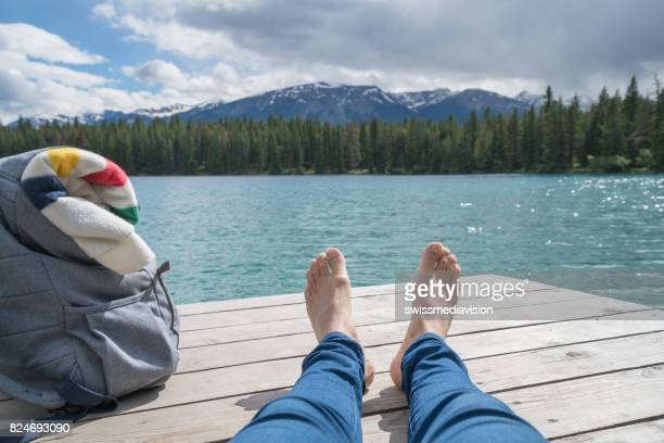 Personal perspective of young man relaxing on lake pier