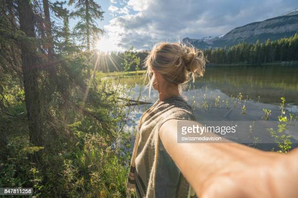 Personal perspective of young woman standing by the lake at sunset