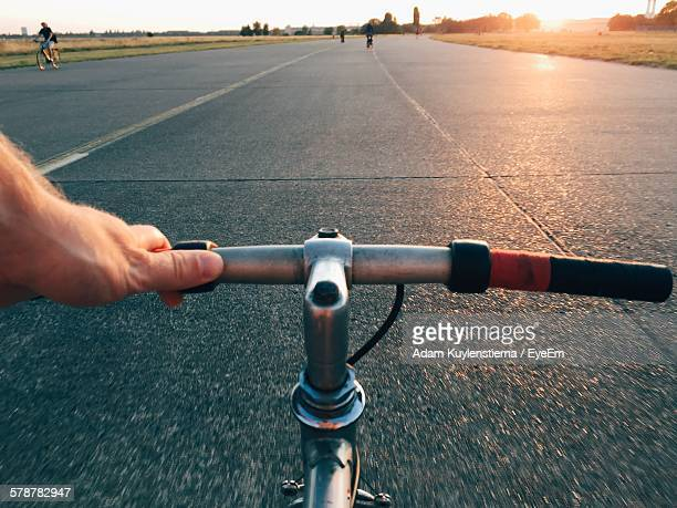 Personal Perspective Shot Of Man Riding Bicycle On Abandoned Airstrip