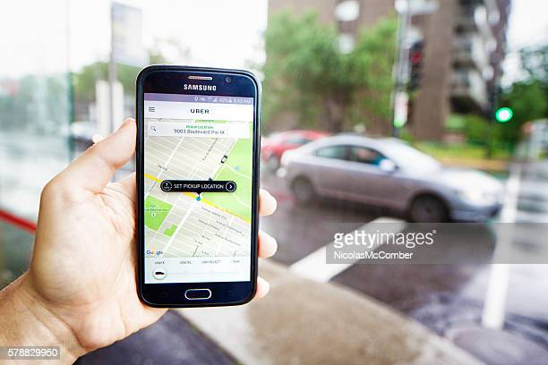 Personal perspective view of hand holding phone ordering Uber ride