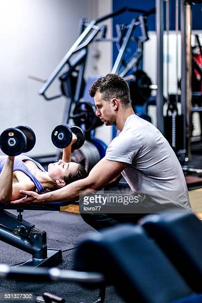 Personal trainer and woman at the gym