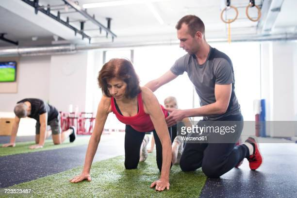 Personal trainer assisting senior woman in gym
