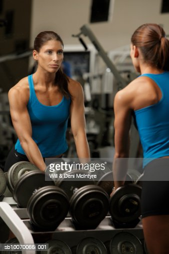 Personal trainer by weight rack, reflecting in mirror : Stock Photo