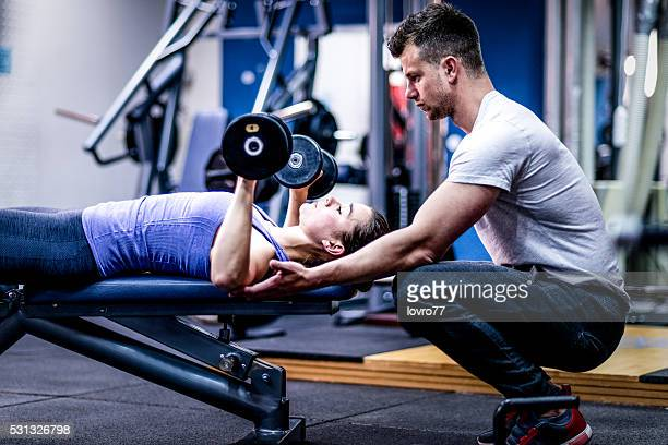 Personal trainer caring woman with her workout