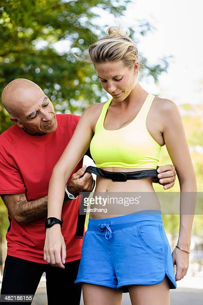 Personal trainer checking athletes heart rate monitors