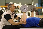 Personal trainer coaching with weights.