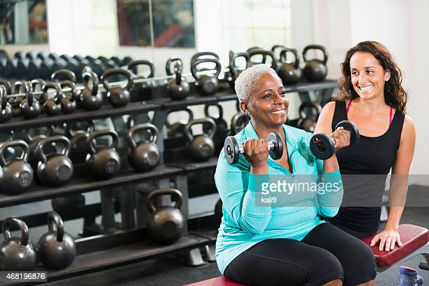 Personal trainer helping African American senior at gym