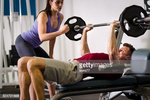 Personal trainer helping man with his workout