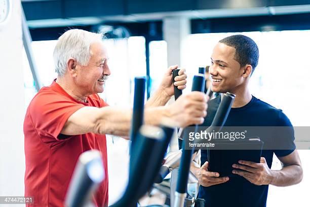 Entraîneur personnel aidant Senior Homme dans la salle de sport