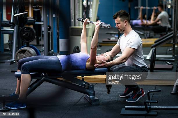 Personal trainer helping woman with her workout