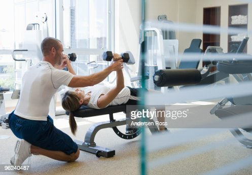 personal trainer helping woman work out : Stock Photo