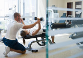 personal trainer helping woman work out