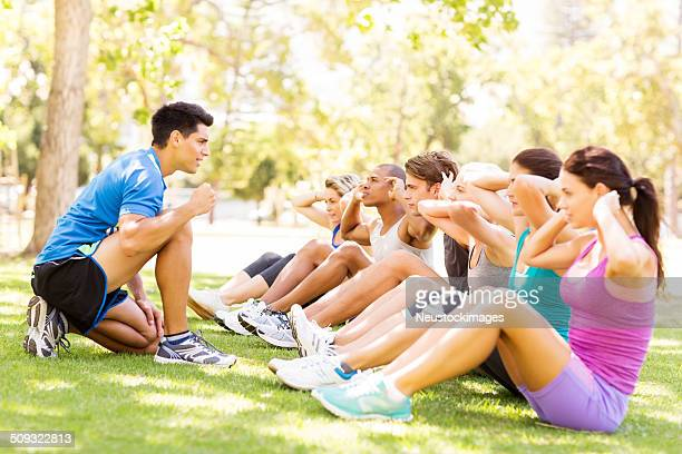 Personal Trainer Motivating People In Doing Sit-Ups At Park