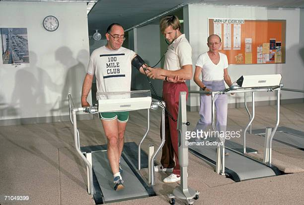 A personal trainer or physical therapist uses a stethoscope to monitor the blood pressure of a man walking on a treadmill in a gymnasium early to mid...