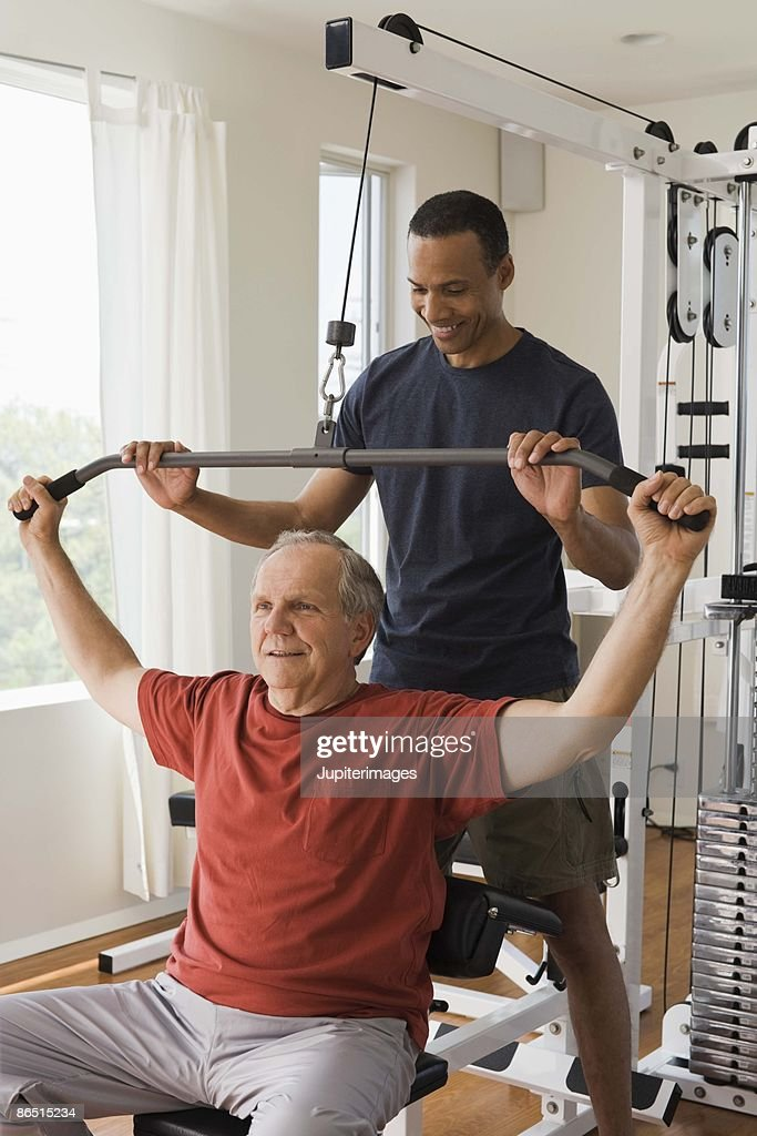 Personal trainer with man in home gym stock photo getty