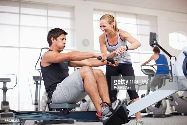 Treinador pessoal com homem sobre a Máquina de Remar no ginásio