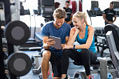 Smiling personal trainer using digital tablet while talking to blonde woman at gym. Happy couple using tablet in fitness club. Client trainer looking at computer her progress at the gym.