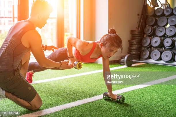 Personal trainers instruct women to make dumbbells at the gym