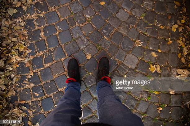 Personal view of feet man on a stone pavement with autumn leafs in Europe.