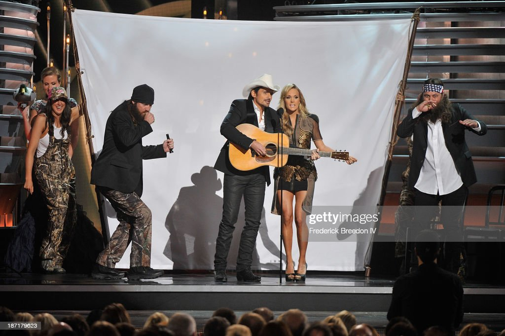 TV Personalities Jace Robertson (2nd from left) and Willie Robertson (R) from the hit show 'Duck Dynasty' on stage with Hosts Brad Paisley (center left) and Carrie Underwood (2nd from right) during the 47th annual CMA awards at the Bridgestone Arena on November 6, 2013 in Nashville, Tennessee.