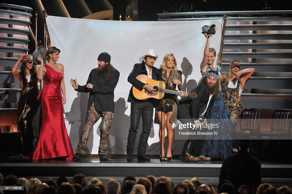 TV Personalities Melissa Robertson (2nd from left), Jace Robertson (3rd from left), Willie Robertson (2nd from right) and Korie Robertson (R) from the hit show 'Duck Dynasty' on stage with Hosts Brad Paisley (center left) and Carrie Underwood (center right) during the 47th annual CMA awards at the Bridgestone Arena on November 6, 2013 in Nashville, Tennessee.