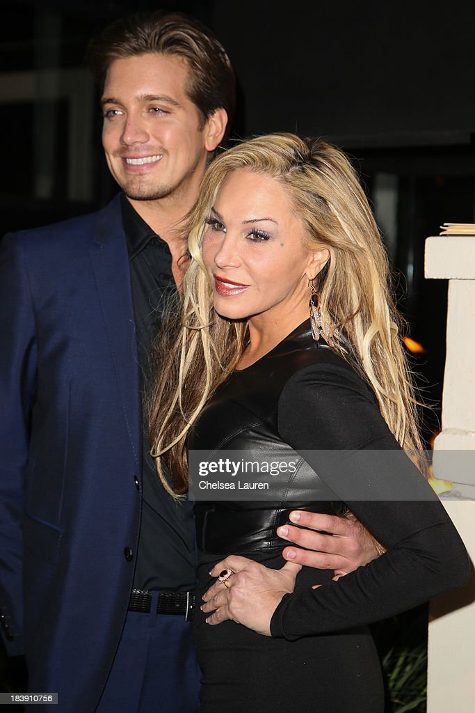TV personality Adrienne Maloof (R) and Jacob Busch arrive at Life & Style's Hollywood in Bright Pink event hosted by Giuliana Rancic at Bagatelle on October 9, 2013 in Los Angeles, California.