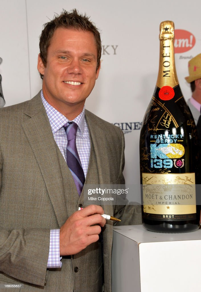 TV personality Bob Guiney signs the Moet Chandon 6L for the Churchill Downs Foundation during the 139th Kentucky Derby at Churchill Downs on May 4...