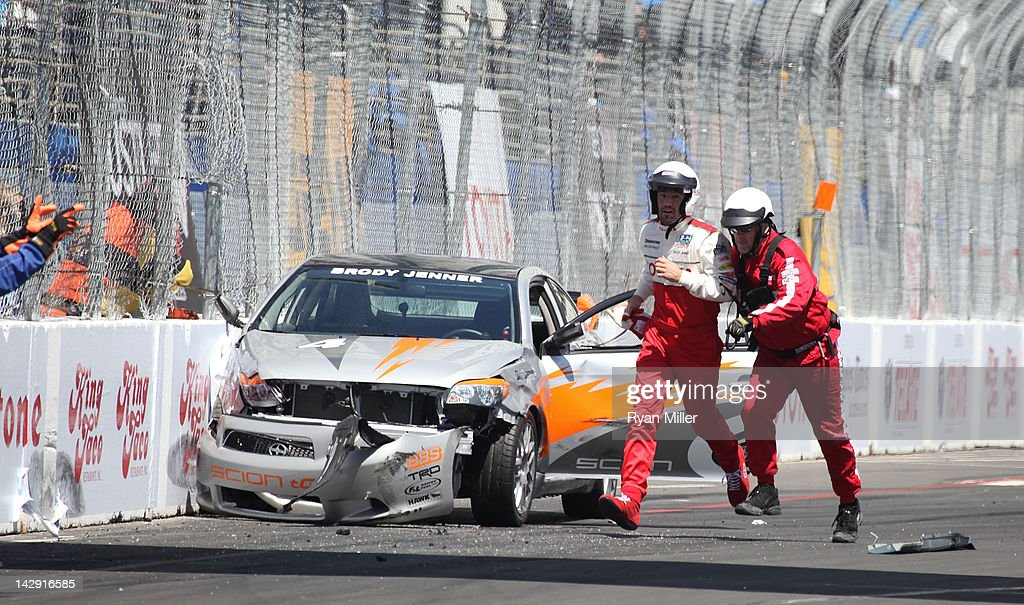 TV Personality Brody Jenner (L) runs off the track with a safety crew member after crashing his car during the 36th Annual Toyota Pro/Celebrity Race held at the Toyota Grand Prix of Long Beach on April 14, 2012 in Long Beach, California.