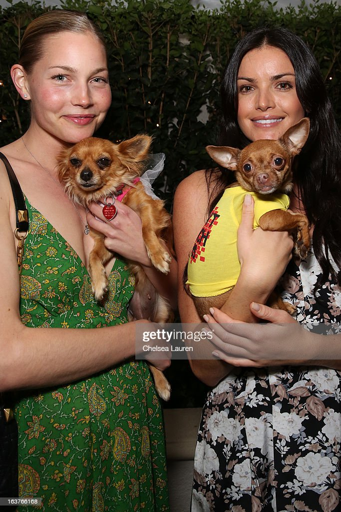 TV personality Courtney Robertson (R) and guest pose with dogs wearing Lyric Culture for PetSmart at Much Love Animal Rescue's makeovers for mutts at Peninsula Hotel on March 14, 2013 in Beverly Hills, California.
