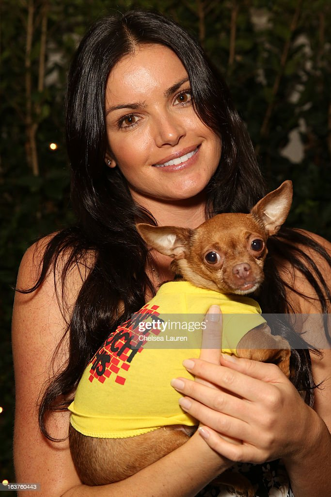 TV personality Courtney Robertson poses with a dog wearing Lyric Culture for PetSmart at Much Love Animal Rescue's makeovers for mutts at Peninsula Hotel on March 14, 2013 in Beverly Hills, California.