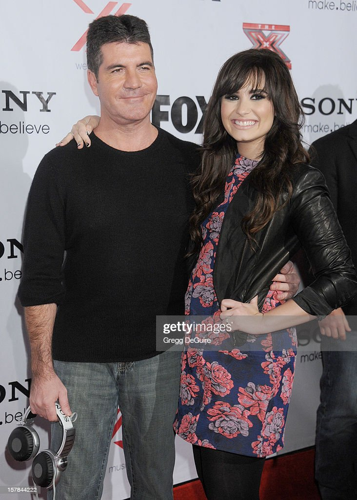 TV personality Simon Cowell and actress/singer Demi Lovato arrive at FOX's 'The X Factor' viewing party at Mixology101 & Planet Dailies on December 6, 2012 in Los Angeles, California.