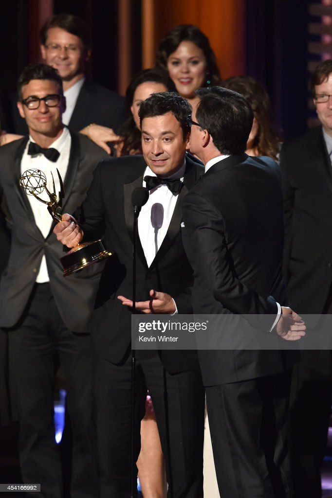 TV personality Stephen Colbert accepts Outstanding Variety Series for 'The Colbert Report' from TV personality Jimmy Fallon onstage at the 66th...