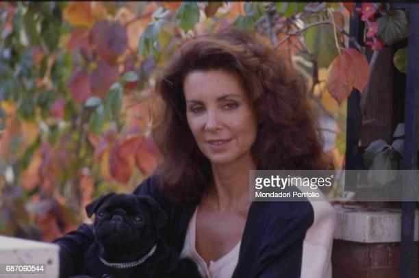 TV personality stylist and socialite italiana Marina Ripa di Meana posing with her dog in her lap November 1987