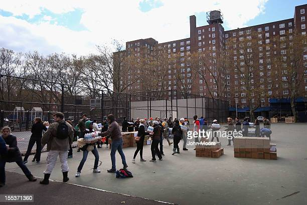 Personel from New York Mayor Michael Bloomberg's office deliver food to the Red Hook public housing project on November 3 2012 in the Brooklyn...