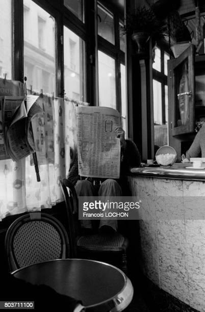 Personne lisant le journal dans un café à Sartrouville en novembre 1976 en France