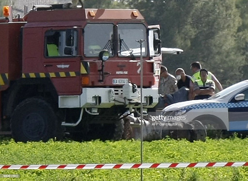 Personnel carry a bag to a forensic van behind a firefighter truck as wreckache of a crashed Eurofighter plane is seen on the ground near a military base at Albacete, 300 kilometres (180 miles) southeast of Madrid on October 12, 2017. A Spanish Eurofighter jet crashed today after taking part in a military display in Madrid for Spain's national day, killing its pilot, the defence ministry said. PHOTO / Luis VIZCAINO