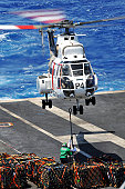 Pacific Ocean, April 9, 2011 - Chief Logistics Specialist attempts to connect a cargo pendant to an SA-330 Puma helicopter as it hovers over the aircraft carrier USS Ronald Reagan.