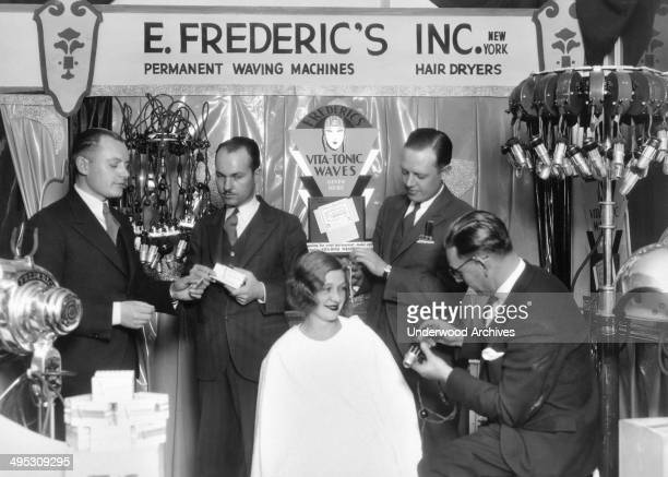 Personnel from the E Frederic's Company demonstrate their permanent waving machines and hair dryers on a woman New York New York circa 1928