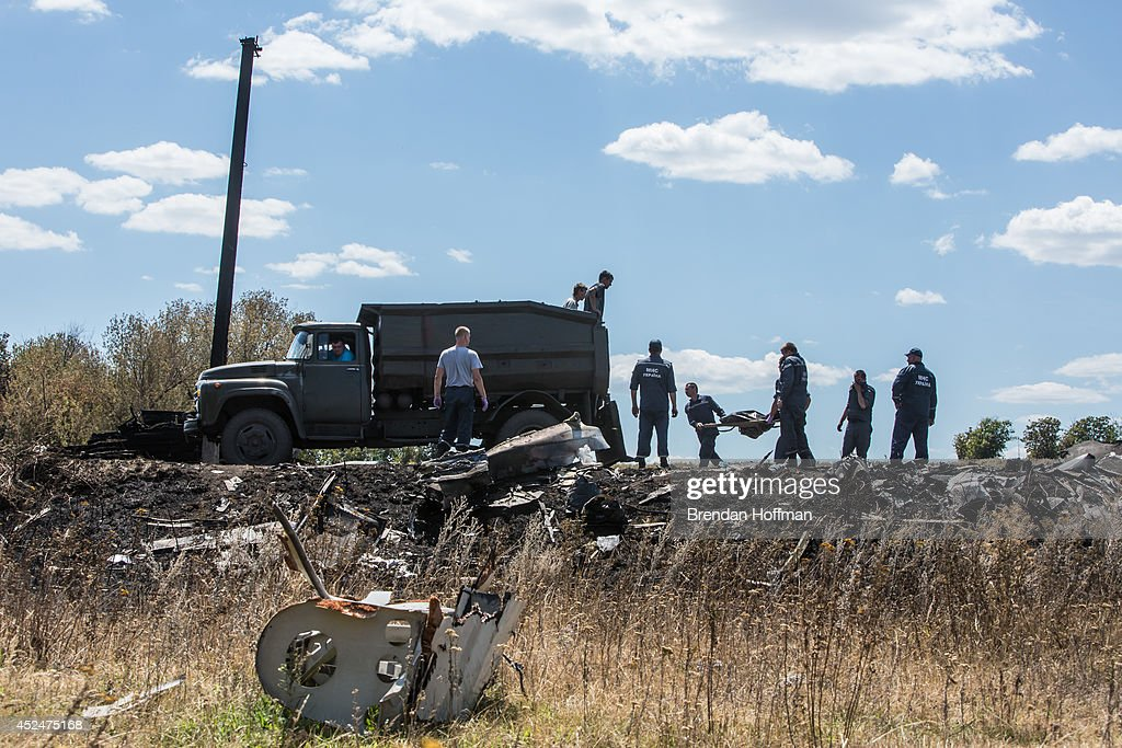 Personnel from the Ukrainian Emergencies Ministry load the bodies of victims of Malaysia Airlines flight MH17 into a truck at the crash site on July 21, 2014 in Grabovo, Ukraine. Malaysia Airlines flight MH17 was travelling from Amsterdam to Kuala Lumpur when it crashed killing all 298 on board including 80 children. The aircraft was allegedly shot down by a missile and investigations continue over the perpetrators of the attack.