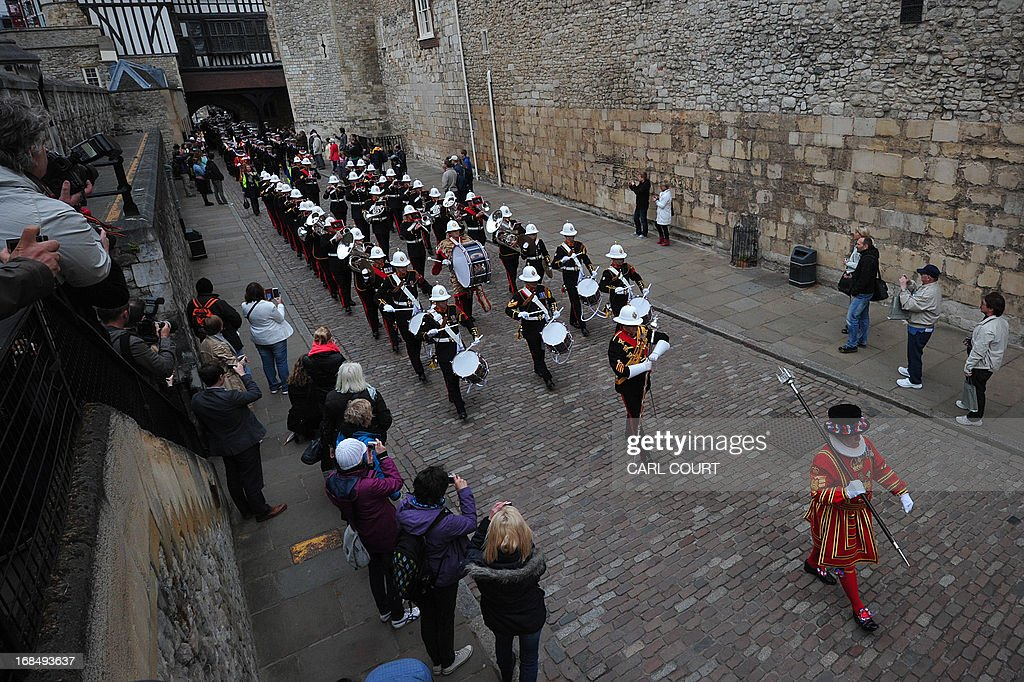 Personnel from three British Royal Navy ships, HMS Illustrious, Edinburgh and Blythe, led by a Yeomen Warder, march through the Tower of London in central London on May 10, 2013 as they deliver barrels of wine representing the dues as they take part for the first time in the historic ceremony of the Constable's Dues. The annual event can be traced back to the 14th century and is related to the Crown's authority over the City of London. During the Middle Ages, successive Kings believed it was their right to extract tolls from vessels on the Thames. On the King's behalf, the Constable of the Tower of London, was empowered to demand these tolls as a perquisite of his office. Past offerings have included barrels of rum, or oysters, mussels and cockles; this year, the Tower's Constable, General Lord Richard Dannatt, was presented with a barrel of wine. AFP PHOTO / CARL COURT