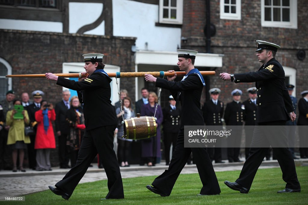 Personnel from three British Royal Navy ships, HMS Illustrious, Edinburgh and Blythe, deliver a barrel of wine representing the dues at the Tower of London in central London on May 10, 2013 as they take part for the first time in the historic ceremony of the Constable's Dues. The annual event can be traced back to the 14th century and is related to the Crown's authority over the City of London. During the Middle Ages, successive Kings believed it was their right to extract tolls from vessels on the Thames. On the King's behalf, the Constable of the Tower of London, was empowered to demand these tolls as a perquisite of his office. Past offerings have included barrels of rum, or oysters, mussels and cockles; this year, the Tower's Constable, General Lord Richard Dannatt, was presented with a barrel of wine. AFP PHOTO / CARL COURT