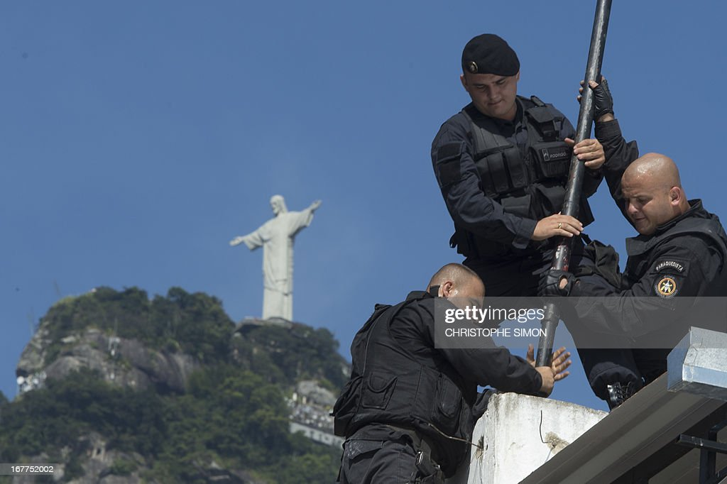 Personnel of Rio de Janeiro's feared military police battalion BOPE, raise the falg of the specially-trained police force known as Police Pacification Units or UPP during an operation at Guararapes shantytown on April 29, 2013 before the UPP can be deployed in. The operation, jointly held by the BOPE, the Shock Battalion and the Canine Operations Unit (BAC), is part of a government strategy designed to combat crime and reassert full control of the Rio de Janeiro metropolis ahead of the upcoming FIFA Confederations Cup, the football World Cup of 2014 and the Olympic Games two years later.