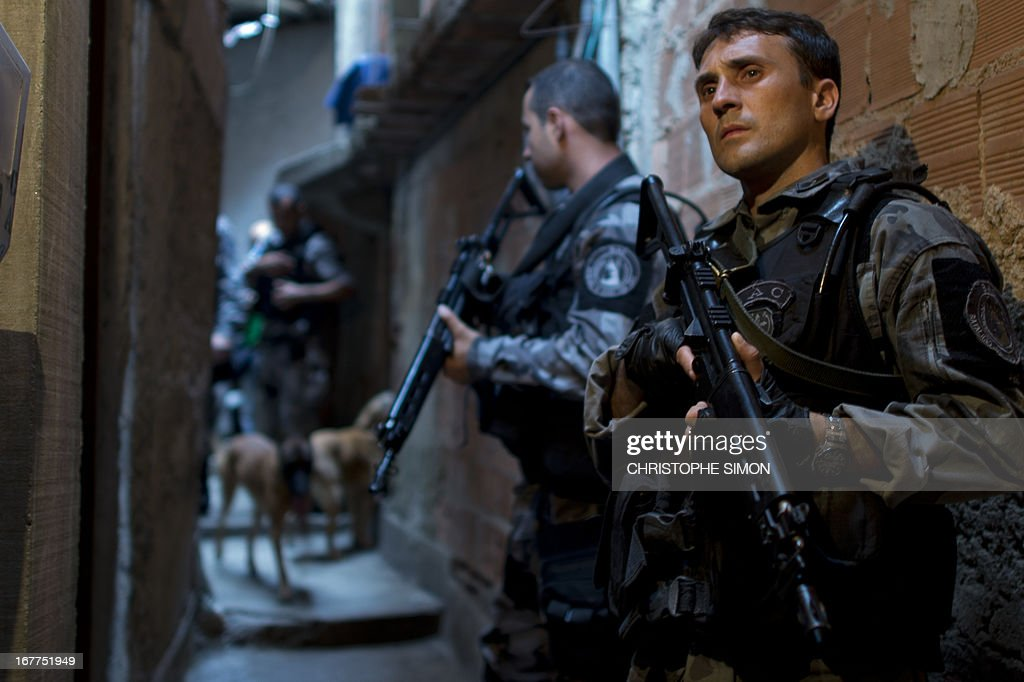 Personnel of the Canine Operations Unit (BAC) carry out an operation at Guararapes shantytown on April 29, 2013 before the specially-trained police force known as Police Pacification Units or UPP, can be deployed in. The operation is part of a government strategy designed to combat crime and reassert full control of the Rio de Janeiro metropolis ahead of the upcoming FIFA Confederations Cup, the football World Cup of 2014 and the Olympic Games two years later.