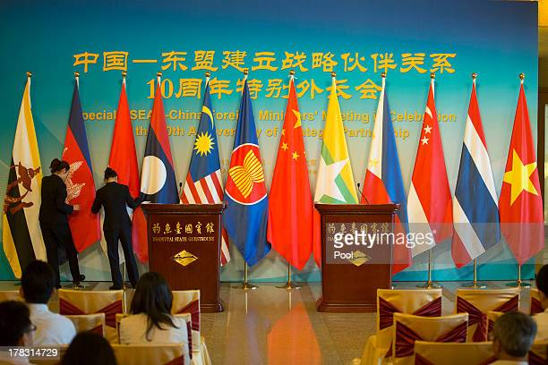 Personnel prepare flags before a press briefing for the first meeting of the opening session of the ASEAN Foreign Ministers meeting at the Diaoyutai...