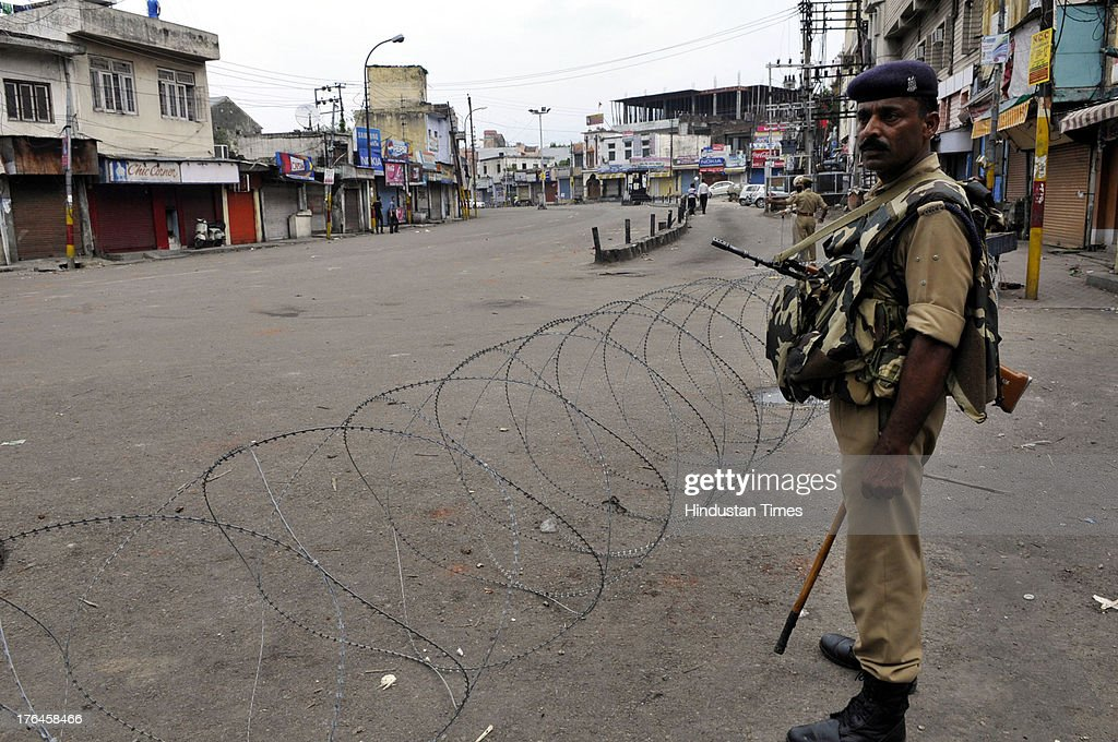 Personnel standing near a barbed wire during a curfew on August 13, 2013 in Jammu, India. Curfew continued in the eight districts of Jammu, Kathua, Samba, Reasi, Udhampur, Rajouri, Doda and Kishtwar districts of Jammu region. Loudspeaker-fitted police vehicles announced in the morning that curfew was in force in these districts and that people should remain indoors. While curfew continued for the fifth day in Kishtwar district where it was imposed on Friday following communal clashes, in other districts it continued for the fourth day on Tuesday. Police arrested 11 people in connection with the communal clashes in Kishtwar.