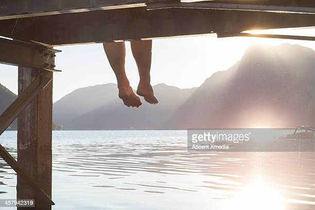 Person's feet dangle form wooden dock, above lake