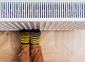 Person's feet in bright yellow-black socks warming them against an heating radiator. Copy-space.