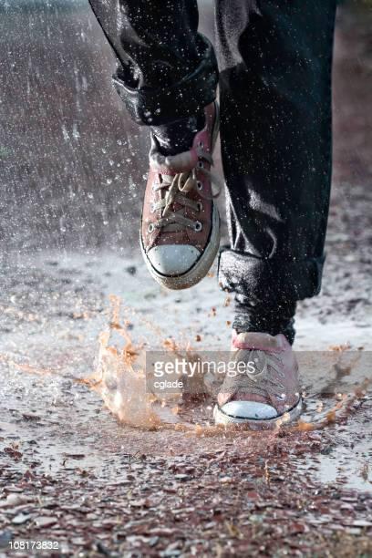 Person, die Füße in Turnschuhen Laufen durch schlammigen Pfütze